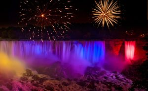Niagara Falls at night in rainbow colors with fireworks