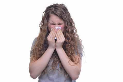 花粉症でくしゃみをする外国人